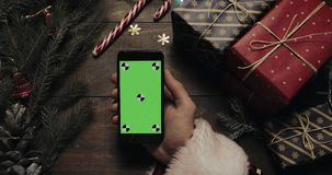 Χέρια Άγιου Βασίλη που κρατά το μαύρο smartphone με την πράσινη οθόνη Άλλα χέρια που τοποθετούν μερικά παρόντα πεδία στον πίνακα φιλμ μικρού μήκους