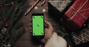 Χέρια Άγιου Βασίλη που κρατά το μαύρο smartphone με την πράσινη οθόνη Άλλα χέρια που τοποθετούν μερικά παρόντα πεδία στον πίνακα απόθεμα βίντεο