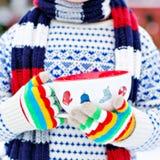 Χέρια λίγου παιδιού που κρατά το μεγάλο φλυτζάνι με snowflakes και το καυτό CH Στοκ Εικόνες