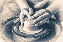 Χέρια αγγειοπλαστών που δημιουργούν ένα προϊόν από τον άργιλο στη ρόδα αγγειοπλαστών ` s παλαιός τρύγος ύφους Στοκ Εικόνες