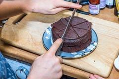 Χέρια αγοριών εφήβων κινηματογραφήσεων σε πρώτο πλάνο που κόβουν το κέικ σοκολάτας στο πιάτο στον ξύλινο πίνακα με το μαχαίρι Στοκ Εικόνα