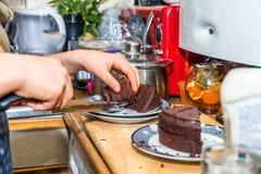 Χέρια αγοριών εφήβων κινηματογραφήσεων σε πρώτο πλάνο που κόβουν το κέικ σοκολάτας στο πιάτο στον ξύλινο πίνακα με το μαχαίρι Στοκ εικόνα με δικαίωμα ελεύθερης χρήσης