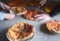 Χέρια αγοριών που κόβουν την πίτσα στοκ φωτογραφία με δικαίωμα ελεύθερης χρήσης