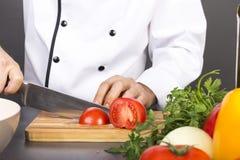 Χέρια αρχιμάγειρα που κόβουν την κόκκινη φρέσκια ντομάτα Στοκ Φωτογραφία