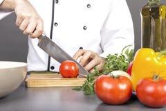 Χέρια αρχιμάγειρα που κόβουν την κόκκινη φρέσκια ντομάτα Στοκ Εικόνες