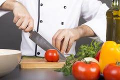 Χέρια αρχιμάγειρα που κόβουν την κόκκινη φρέσκια ντομάτα Στοκ εικόνες με δικαίωμα ελεύθερης χρήσης