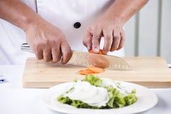 Χέρια αρχιμάγειρα που κόβουν την ντομάτα Στοκ Εικόνα
