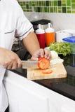 Χέρια αρχιμάγειρα που κόβουν την ντομάτα Στοκ Εικόνες