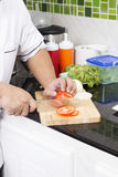 Χέρια αρχιμάγειρα που κόβουν την ντομάτα Στοκ Φωτογραφία