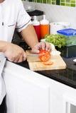 Χέρια αρχιμάγειρα που κόβουν την ντομάτα Στοκ εικόνα με δικαίωμα ελεύθερης χρήσης