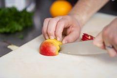 Χέρια αρχιμάγειρα που κόβουν τη Apple στον τεμαχίζοντας πίνακα Στοκ Εικόνα