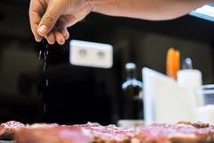 Χέρια αρχιμάγειρα tenderloin βόειου κρέατος εποχής, με το υπόβαθρο ελαφρώς στοκ φωτογραφία με δικαίωμα ελεύθερης χρήσης
