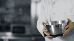 Χέρια αρχιμαγείρων που έχουν τη διασκέδαση με το κύπελλο χάλυβα σε σε αργή κίνηση Άτομο αρχιμαγείρων που προετοιμάζεται να μαγειρ απόθεμα βίντεο