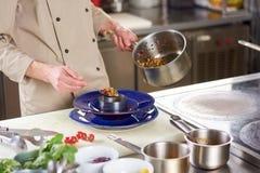 Χέρια αρχιμαγείρων που βάζουν τα λαχανικά ratatouille στο πιάτο Στοκ φωτογραφία με δικαίωμα ελεύθερης χρήσης