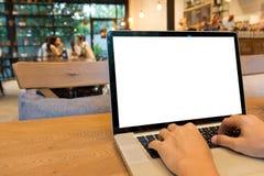Χέρια ατόμων που δακτυλογραφούν στο lap-top με την κενή άσπρη οθόνη στην ξύλινη ετικέττα στοκ φωτογραφία με δικαίωμα ελεύθερης χρήσης