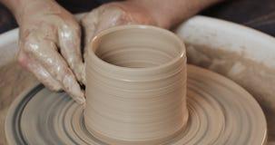 Χέρια ατόμων που δημιουργούν το βάζο ή το βάζο του άσπρου αργίλου Στριμμένη ρόδα αγγειοπλαστών ` s Χειροποίητος, τέχνη φιλμ μικρού μήκους
