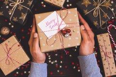 Χέρια ατόμων που κρατούν το κιβώτιο δώρων διακοπών Χριστουγέννων με τα εύθυμα Χριστούγεννα καρτών στο διακοσμημένο εορταστικό πίν Στοκ Φωτογραφίες