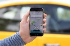 Χέρια ατόμων που κρατούν το iPhone με το ταξί Uber εφαρμογής στην οθόνη Στοκ Εικόνα