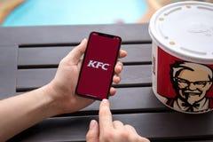 Χέρια ατόμων που κρατούν το iPhone Χ με app το τηγανισμένο το Κεντάκυ κοτόπουλο Στοκ εικόνα με δικαίωμα ελεύθερης χρήσης