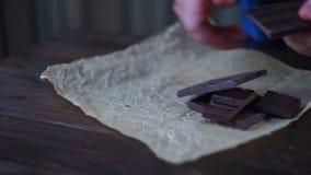 Χέρια ατόμων που σπάζουν τη σκοτεινή σοκολάτα σκοτάδι σοκολάτας ράβδων μακρο γλυκό κομματιών επιδορπίων σοκολάτας φιλμ μικρού μήκους