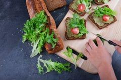 Χέρια ατόμων ` s που κατασκευάζουν τα σάντουιτς σε ένα επιτραπέζιο υπόβαθρο Σάντουιτς με τα πράσινα, ντομάτες, σάλτσα αβοκάντο Μα Στοκ Εικόνες