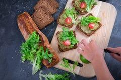 Χέρια ατόμων ` s που κατασκευάζουν τα σάντουιτς σε ένα επιτραπέζιο υπόβαθρο Σάντουιτς με τα πράσινα, ντομάτες, σάλτσα Έννοια προγ Στοκ Φωτογραφίες