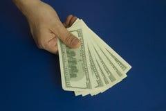 Χέρια ατόμων ` s που κρατούν τα δολάρια στο σκούρο μπλε υπόβαθρο Στοκ φωτογραφία με δικαίωμα ελεύθερης χρήσης