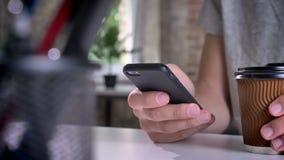 Χέρια ατόμων ` s που κρατούν τον καφέ και που δακτυλογραφούν στο τηλέφωνο κυττάρων στην αρχή φιλμ μικρού μήκους