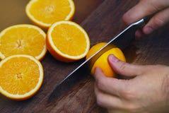 Χέρια ατόμων ` s που κόβουν το φρέσκο πορτοκάλι στην κουζίνα συνοδευόμενος συλλάβετε την ιταλική θέση φωτογραφίας τροφίμων αρχείω Στοκ φωτογραφία με δικαίωμα ελεύθερης χρήσης