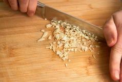 Χέρια ατόμων ` s που κόβουν το φρέσκο σκόρδο στην κουζίνα, που προετοιμάζει ένα γεύμα για το μεσημεριανό γεύμα με το copyspace Στοκ Εικόνες
