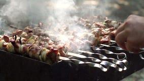 Χέρια ατόμων ` s που περιστρέφονται τα οβελίδια Shish kebab κρέας φιλμ μικρού μήκους