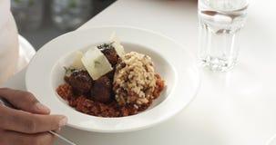 Χέρια ατόμων ` s που τρώνε ένα γεύμα του ρυζιού και των μανιταριών, σουηδικά κεφτή σε ένα κρεβάτι των καρότων με τις φέτες παρμεζ Στοκ Φωτογραφίες
