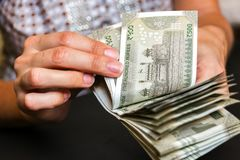 Χέρια γυναίκας με νέα ινδικά 500 τραπεζογραμμάτια ρουπίων