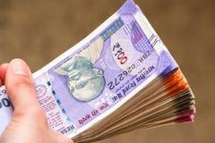 Χέρια γυναίκας με νέο Ινδό 100, 200, 500, 2000 τραπεζογραμμάτια ρουπίων