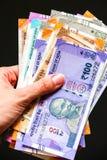 Χέρια γυναίκας με ολοκαίνουργιο Ινδό 50, 100, 200, 500, 2000 τραπεζογραμμάτια ρουπίων