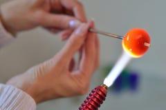 Χέρια γυναίκας με τα εργαλεία για το γυαλί που λειώνει, ο χρόνος του producti Στοκ Εικόνες