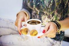 Χέρια γυναίκας με τα χρυσά βραχιόλια, το φλιτζάνι του καφέ και το πρόχειρο φαγητό Στοκ φωτογραφία με δικαίωμα ελεύθερης χρήσης