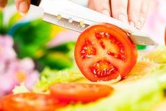 Χέρια γυναίκας που κόβουν την ντομάτα Στοκ Εικόνες