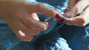 Χέρια γυναίκας που πλέκουν το μπλε πουλόβερ φιλμ μικρού μήκους
