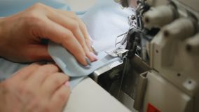 Χέρια γυναίκας που ράβουν ένα overlock στη ράβοντας μηχανή Βελονιά Overlock στη ράβοντας μηχανή Αυτόματη ράβοντας μηχανή φιλμ μικρού μήκους