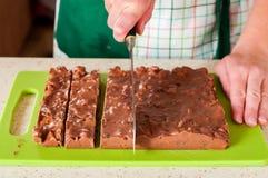 Χέρια γυναίκας που τεμαχίζουν τη σοκολάτα, το μπισκότο, σουλτάνα και το ξύλο καρυδιάς Fudg Στοκ Φωτογραφία