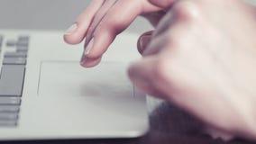 Χέρια γυναίκας που χρησιμοποιούν ένα trackpad σε έναν φορητό υπολογιστή φιλμ μικρού μήκους