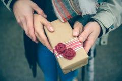 Χέρια γυναικών και ανδρών που παρουσιάζουν otdoors κιβωτίων δώρων Στοκ Εικόνες