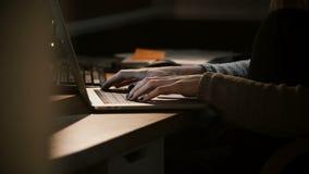 Χέρια γυναικών κινηματογραφήσεων σε πρώτο πλάνο που χρησιμοποιούν το lap-top στο σκοτάδι Θηλυκή δακτυλογράφηση στο πληκτρολόγιο σ φιλμ μικρού μήκους