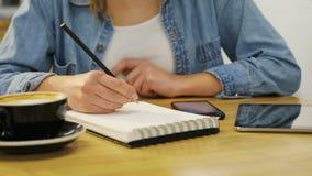 Χέρια γυναικών κινηματογραφήσεων σε πρώτο πλάνο που κρατούν το smartphone και που γράφουν στο σημειωματάριο στον καφέ με τα ξύλιν απόθεμα βίντεο