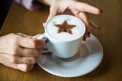 Χέρια γυναικών με ένα καυτό φλιτζάνι του καφέ Καφές με το γάλα, latte Ένα φλιτζάνι του καφέ στον πίνακα Αγκάλιασμα ενός φλιτζανιο Στοκ Φωτογραφία