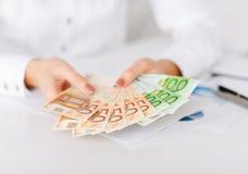 Χέρια γυναικών με τα ευρο- χρήματα μετρητών Στοκ Φωτογραφία