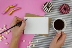 Χέρια γυναικών με τη ρομαντική επιστολή Τοπ άποψη, flatlay Πρότυπο προτύπων Το ρομαντικό πρωί κινητήριο, τσάι, αυξήθηκε και γλυκά Στοκ Εικόνες
