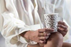 Χέρια γυναικών με τον καυτό καφέ Στοκ Φωτογραφία
