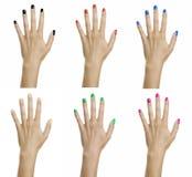 Χέρια γυναικών με το ζωηρόχρωμο βερνίκι καρφιών Στοκ Εικόνες